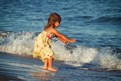Little girl and the sea. Little girl trying to catch/hug the wave Stock Image