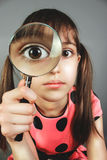 Little girl searching with magnifying glass. Little child girl searching with magnifying glass stock images