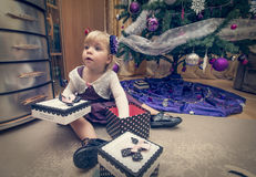 Little girl searching for presents near the Christmas tree Royalty Free Stock Photo