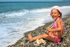 Little girl with seashell and necklace on seacoast Stock Photos