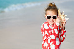 Little girl with a seashell Stock Images