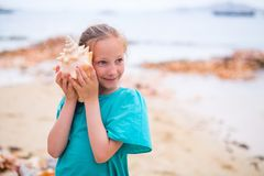Little girl with a seashell. Portrait of adorable little girl with a seashell stock image