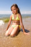 Little girl at the seaside. Little girl sitting in water of a sea at day Stock Photo