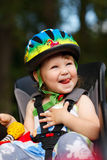 Little girl in the seat bicycle with a helmet Stock Photo