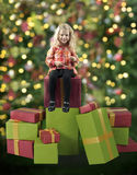 Little girl seated on christmas presents Stock Images