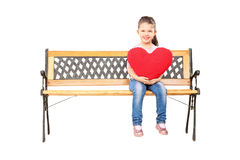 Little girl seated on wooden bench holding a big red heart Stock Photos
