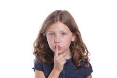 Little Girl Secret. A cute little girl holds her finger over her mouth to shush Stock Photography