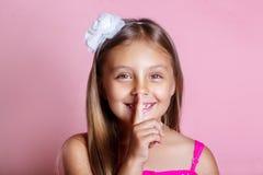 Little girl with a secret . Closeup headshot. Stock Photo