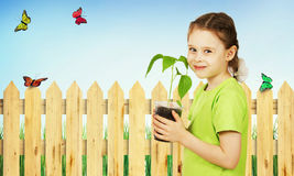 Little girl with a seedling in the pot in the garden Stock Images