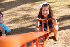 Little girl in a seesaw Stock Images