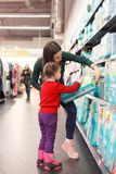 Little girl selecting diapers in supermarket with her mom.  Royalty Free Stock Photos
