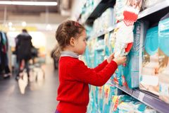 Little girl selects diapers in supermarket.  Stock Photography