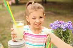 Little girl selling natural lemonade in park Royalty Free Stock Image