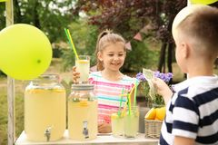 Little girl selling lemonade at stand in park. Little girl selling natural lemonade at stand in park stock photography