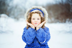 Little girl sends a kiss, playing in the snow park. Stock Photography
