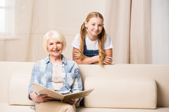 Little girl and senior woman with photo album smiling at camera Royalty Free Stock Image