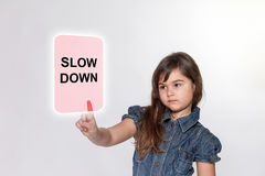 Little girl with is touching a transparent rectangle. Little girl with a serious expression is touching a pink transparent rectangle with inscription Slow Down Royalty Free Stock Photography