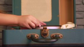 Girl music sets record. A little girl sets a vinyl music record on an old gramophone and includes it in closeup stock footage