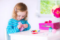 Little girl sewing a dress for her doll Stock Photo
