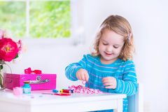 Little girl sewing a dress for her doll Stock Image