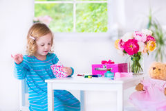 Little girl sewing a dress for her doll Stock Photos