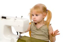 The little girl and a sewing machine Stock Photo