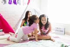 Girl Sharing Secret With Friend During Sleepover Party. Little girl sharing secret with best friend during sleepover party at home stock photo