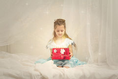 Little girl with a shining box Stock Image