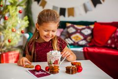 Little girl in red dress eating Christmas cookies with cacao in cup, red Chirstmas decorations around royalty free stock photography