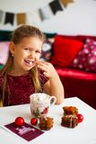 Little girl in red dress eating Christmas cookies with cacao in cup, red Chirstmas decorations around stock image