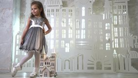 A little girl in a shiny dress and white shoes posing near a toy castle, slow motion stock footage