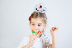 Little girl in shiny princess crown eats candy Royalty Free Stock Image