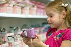 Little girl in a shoe store. A little girl in a shoe store holding shoe Stock Images
