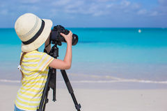 Little girl shooting with camera on tripod during Stock Photos