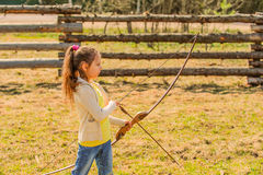 Little girl shoots bow Stock Photography