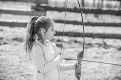 Little girl shoots bow Stock Image