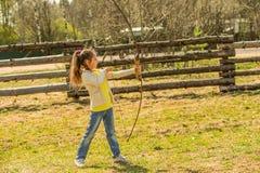 Little girl shoots bow Stock Photos