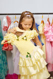 Little girl in shop of dresses Stock Images