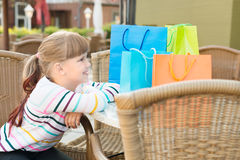 Little girl with shoping bags at outdoor cafe Royalty Free Stock Photo