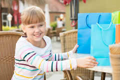 Little girl with shoping bags at outdoor cafe Stock Photos