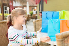 Little girl with shoping bags at outdoor cafe Royalty Free Stock Image