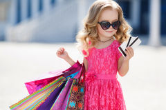 Little girl with shopping bags goes to the store Stock Photos