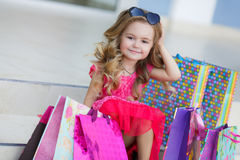 Little girl with shopping bags goes to the store Stock Photo