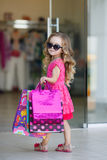 Little girl with shopping bags goes to the store. Cute little girl on shopping. portrait of a kid with shopping bags. child in dress, sunglasses and shoes near royalty free stock images