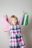 Little girl with shopping bags and lollipop. Cute little girl with shopping bags eating a lollipop Royalty Free Stock Photography