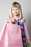 Little girl with shopping bags and lollipop. Cute little girl with shopping bags and a heart lollipop Stock Photos