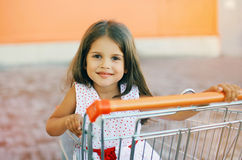 Little girl in shopping cart. Outdoors Stock Photo