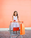 Little girl in shopping cart outdoors Royalty Free Stock Photos