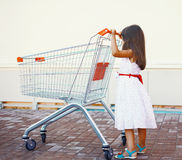 Little girl with shopping cart outdoors Stock Photos