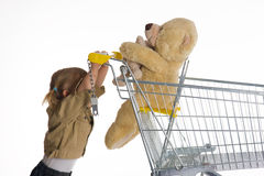 Little girl with shopping cart and  Teddybear Royalty Free Stock Photos